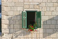 Window with red flowers. And green shutters on yellow stone building wall Royalty Free Stock Photo
