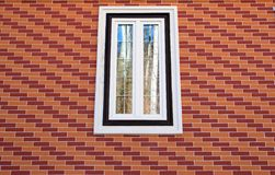 Window on a red and orange brick wall pattern Royalty Free Stock Images