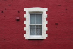 Window in red wall. White framed window in a painted red brick wall stock images