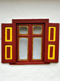 Window with red and yellow wooden shutters white wall Royalty Free Stock Images