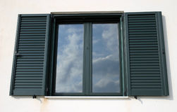 Window reflection. Window with open shutters reflecting the sky stock images