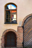 Window with reflection and old gate in the old town Royalty Free Stock Images