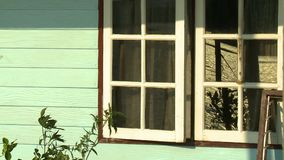 Window With Reflection of Sea. Steady, medium close up shot of two windows on a house, a reflection of the sea can be seen stock video footage
