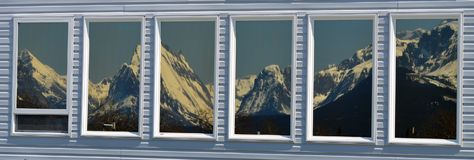 Window reflection of snow covered mountains !. These windows are beautifully reflecting the majestic snow covered mountains which are across the field Stock Photos