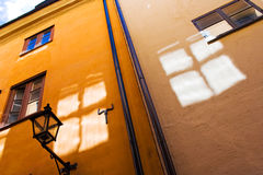 Window reflections on old town walls. Bright windows sun reflection on old town walls under blue sky Stock Photography