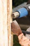 Window renovation. Windows renovation: removing old paint using scraper and heat gun Stock Images