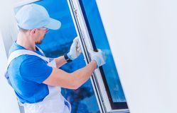Window Replacement. Installation by Professional Caucasian Construction Worker. Home Building or Remodeling Photo Concept stock image