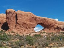 Window Rock at Arches National Park, with hikers walking toward it. And bushes in the foreground stock photos