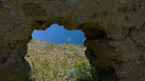 Window in the rock. A hole in the masonry and a view of the sea. Watch through the rock stock video footage