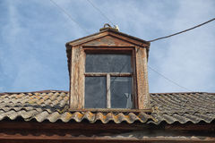A window on the roof of the old rustic house Royalty Free Stock Images