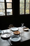 Window Rustic Table Setting. Rough plank dining table set with antique cutlery, plates and glasses royalty free stock photography