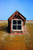 Window on a rusty corrugated iron roof. A rustic window on top of a rusty corrugated iron roof Royalty Free Stock Photos