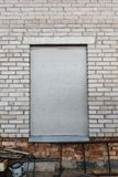 Window`s bricked up. The window is boarded up with gray flat slate. A gray brick wall with a boarded-up window. Grunge stock photos