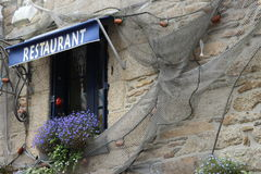 Window of seafood restaurant with flowers and netting. In concarneau Stock Photo