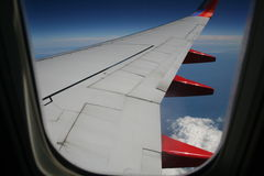 The window seat. Red and white airplane wing seen through the window Royalty Free Stock Photo