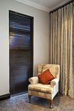Window Seat. Single comfy chair by the window of the bedroom with sophisticated blinds Royalty Free Stock Photography