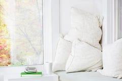 Window seat cushoins. Window seat with cushions, book and mug; fall view stock photos