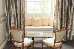 Window seat and drapes. Formal window seat with cloth drapes and chairs in an English mansion parlor or tearoom Royalty Free Stock Image