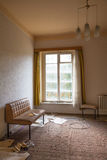 Window seat. An old sofa standing in an empty room at the window Royalty Free Stock Image