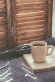 Window seat. Warm and cozy window seat with cushions and a opened book, light through vintage shutters, rustic style home decor. (Text in the book is not Royalty Free Stock Photography