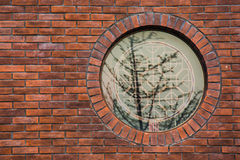 A circular window with shadow on a brick wall. A window with shadow of trees on a red brick wall stock images