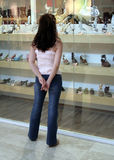 Window shopping. Young woman in jeans window shopping Royalty Free Stock Photos