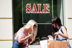 Two happy fashion women with shopping bags at the mall window Royalty Free Stock Photography