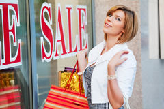 Fashion woman with shopping bags at the mall window Stock Photos