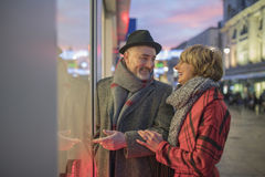 Window Shopping At Christmas. Mature couple are window shopping in the festive city centre at christmas time Royalty Free Stock Photo