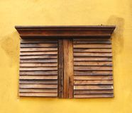 Window shutter. Wooden window shutter on painted wall Royalty Free Stock Photo