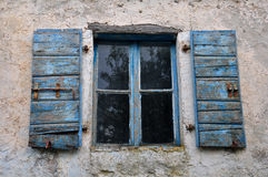 Window shutter chipped paint. Wooden window shutter with chipped blue paint and textured wall of old house Stock Images