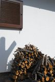 Window shutter and heaped firewood. Window wooden shutter and heaped firewood on white wall Stock Photos