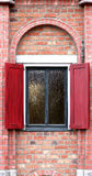 Window with shutters in a brick house Stock Photo