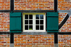 Window with shutters in brick wall of half timbered house Royalty Free Stock Photo