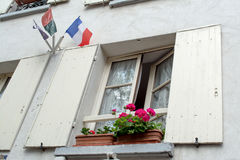 Window with shutters, flag of France and beautiful flowers. Window with shutters and beautiful flowers in Paris Royalty Free Stock Image