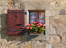 Window with shutters and flowers in old building in Switzerland Stock Image