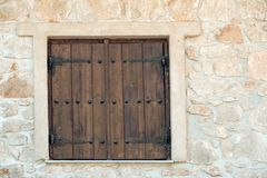 Window shutters on old stone wall. Building facade wall with wooden shutters closed. Architecture structure and design.  royalty free stock photography