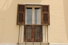 Window Shutters. Wooden window shutters decorate a house in one of the narrow streets of Cagliari on the island of Sardinia, Italy Royalty Free Stock Photography