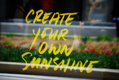 Window sign saying Create Your Own Sunshine. Stock Photo