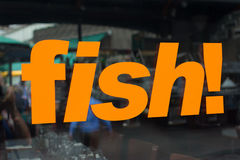 window sign with the word fish in bright orange letters royalty free stock photo