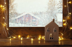 Window sill with christmas lights in front of winter background. Old window sill with gold christmas lights in front of dreamy and magical winter snow landscape stock photo