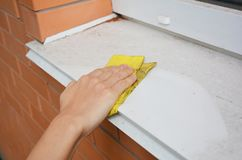 Window Sill Cleaning from Dust. Cleaning Your Windows and Window Sills. Avoid White color in exterior building Royalty Free Stock Photo