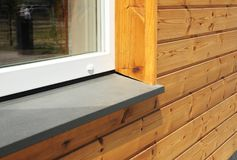 Window Sill with Modern Wooden Facade Wall. Single plastic window sill detail. Install window Royalty Free Stock Image