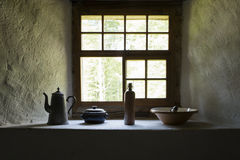 Window sill with vintage household items. View on several vintage household items standing close a somber window sill stock photo