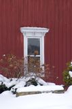 Window in the Snow. A white window in a red building with a snow on the landscaping below Royalty Free Stock Images