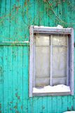 The window with snow on window sill of the on old plank wall painted in bright turquoise color, wild grapes branches without stock images