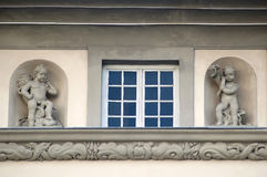Window and statues of cupids in Lviv Royalty Free Stock Photo