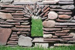 A window in a stone ornamental wall in a city park stock photography