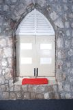 Window in stone wall. A decorative arched window in an old stone wall with red pad on the window sill Royalty Free Stock Photos