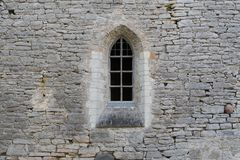 Window in the stone wall of an ancient monastery stock images